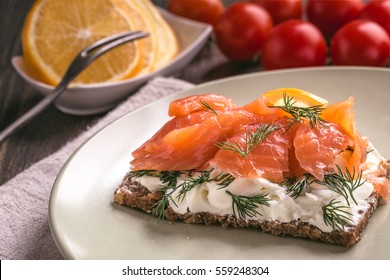 Smoked salmon sandwich with cream cheese on plate close-up shot.