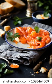 Smoked salmon slices with salted salmon caviar decorated with fresh parsley leaves