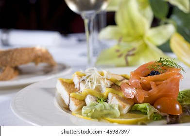 Smoked salmon with toast appetizer on white plate