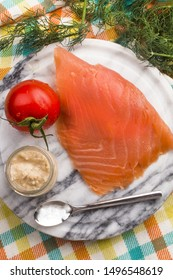 smoked salmon with tomato and horseradish on a round marble plate