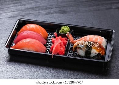 Smoked salmon, Unagi, shrimp, fresh salmon, tuna nigiri sushi in plastic delivery box over slate plate background