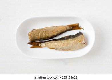 Smoked sardines in a white plate top view