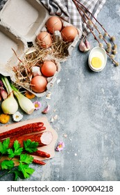 Smoked sausage, eggs and vegetables. Easter food on grey, stone backround.