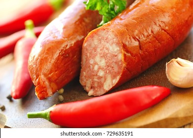 Smoked sausage with spices and greens on the table