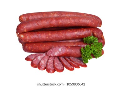 Smoked sausages decorated with sprig of parsley. Appetizing meat product whole and partially sliced. Isolated on white background