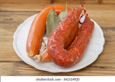 smoked sausages on white plate on brown wooden background