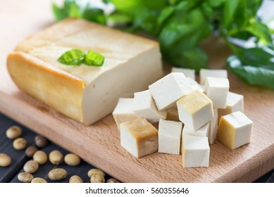 Smoked soy cheese tofu diced on a cutting board, soy beans, basil closeup