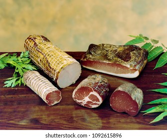 smoked speck, bresaola, pork meat and other kind of stuffed meat on wooden table