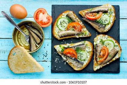 Smoked sprat sandwich - fish, boiled egg, fresh cucumber and tomato, black and white sesame, dill sandwiches on fried bread slices