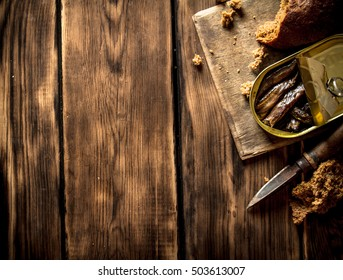 Smoked sprats with rye bread. On wooden background.