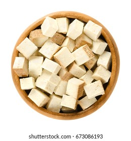 Smoked tofu cubes in wooden bowl. Bean curd. Coagulated soy milk, pressed into firm white blocks. Component of Asian cuisine. Meat substitute. Isolated macro food photo close up from above over white.