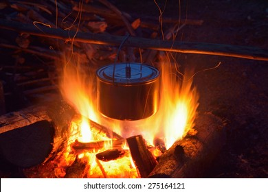 Smoked tourist kettle over camp fire in the evening