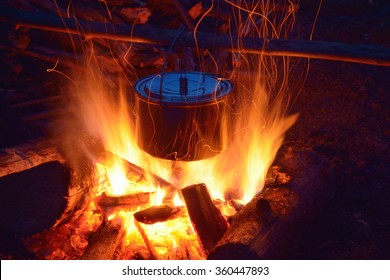 Smoked tourist kettle over camp fire in the evening. Spring mountains.
