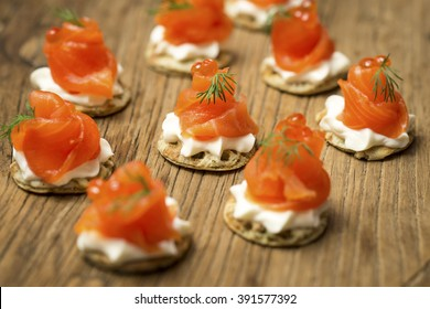 Smoked Trout Canapes with dill and horseradish cream on a textured wooden background