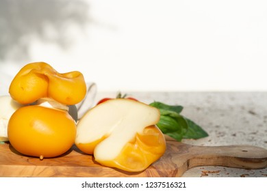 Smoked and white Fresh South Italian traditional cow or cow and sheep semi-soft cheese Scamorza served outdoor on olive wood board