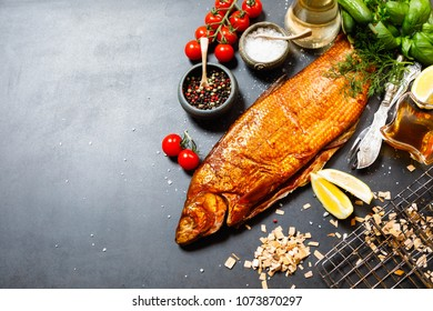 Smoked whitefish with salt and pepper in dish, fork and knife, lemon, basil, tomatoes, little cucumbers, parslay, grid for grilling, cherry wood chunks  on a black background, top view, overhead, flat