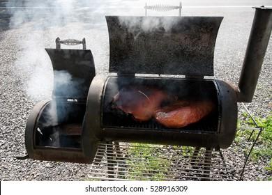 Smoker grill smoking ham and brisket. Horizontal.