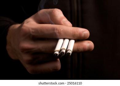 smoker holding three cigarettes