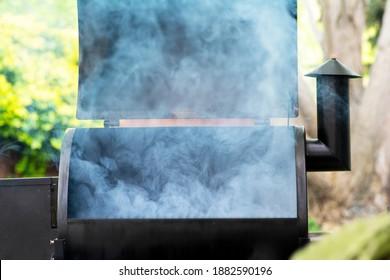 A smoker starting the smoking process, smoke coming from grill.
