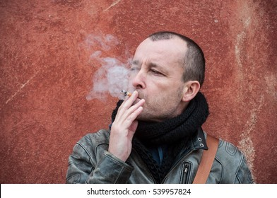 smoker with winter jacket on stoned wall in outdoor