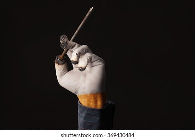 Smokers hand holds a coffin nail like a cigarette