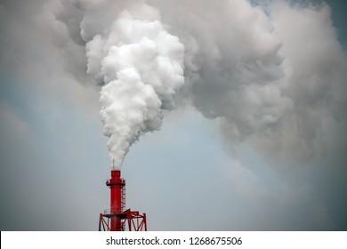 Smokestack billows exhaust gas into blue sky