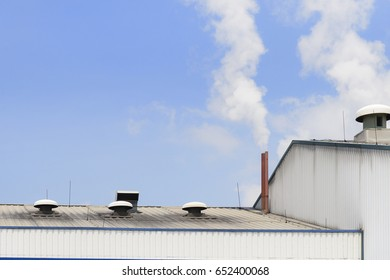 The smokestack of factory building with the smoke and blue sky. Pollution from industrial concept.