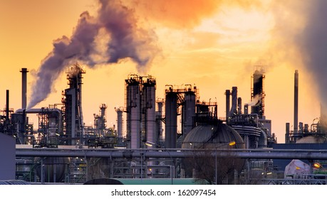 Smokestack in factory with yellow sky and clouds