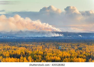 Smokestack that pollute the atmosphere. Ecological catastrophy. Polar tundra, deep autumn. Sunset, bad lighting conditions.