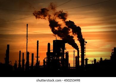 Smokestacks blowing smoke into the atmosphere at sunset