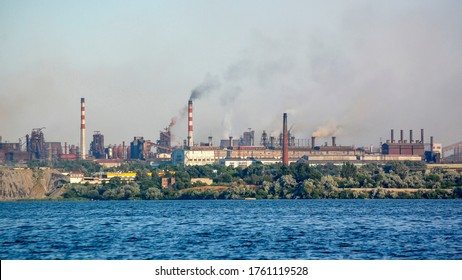 Smokestacks of industrial plants, view from the water