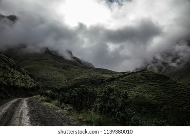 Smokey green mountains with a deep valley where white clouds hanging deep between the hills with shades and light areas with a dirt road leading into the mountains