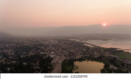 Smokey haze takes over the small Canadian town in the midst of the summer 2018 BC wildfires. Blood Red sun sets behind large rocky mountains. Pond and large lake with wharf are visible.