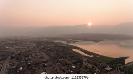 Smokey haze takes over the small Canadian town in the midst of the summer 2018 BC wildfires. Blood Red sun sets behind large rocky mountains.