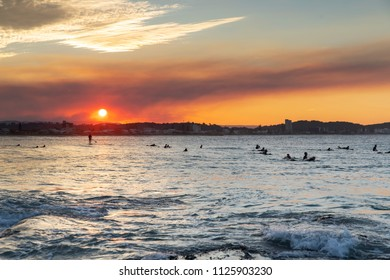 Smokey red sunset with surfers in the water at Currumbin Gold Coast