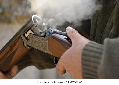 A smoking 12 bore shotgun having ejected spent a cartridge