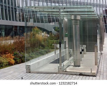 The smoking area near the modern office building is covered with glass panels and equipped with ventilation.