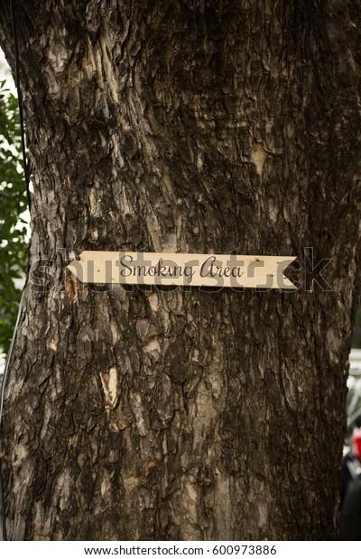 Smoking Area Sign on Tree