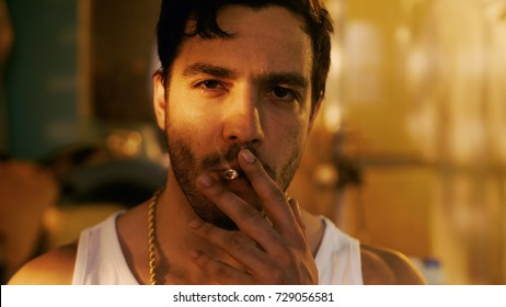 Smoking Brutal Gang Member with Gold Chain Looks into Camera with Defiance. Underground Drug Laboratory is in Background.