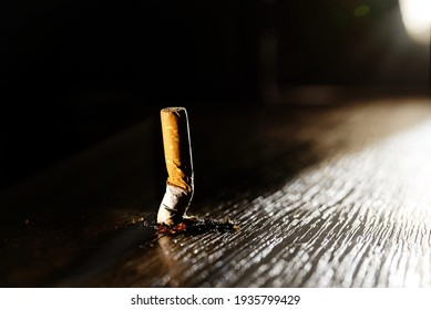 A smoking burning cigarette on a dark floor background. Stop smoking concept