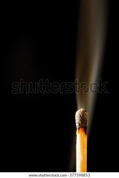 Smoking Burnt Match on Black Background