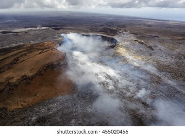 Smoking caldera of the Puu Oo vent with smaller crater in the foreground, Big Island, Hawaii. The lava field created by Puu Oo is in the background. Aerial photograph out of a helicopter.