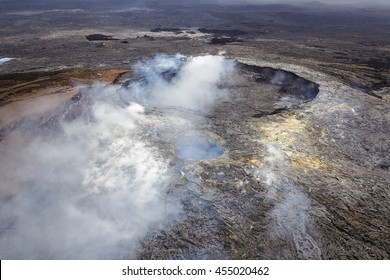 Smoking caldera of the Puu Oo vent with smaller crater in the foreground, Big Island, Hawaii. Aerial photograph out of a helicopter.
