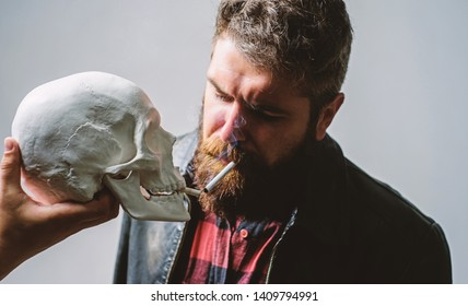 Smoking cause health damage and death. Destroy your health. Smoking is harmful. Habit to smoke tobacco bring harm to your body. Man smoking cigarette near human skull symbol of death. Harmful habits.