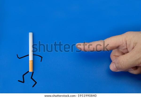 Smoking cessation concept. Index finger drives cigarette on legs on blue background