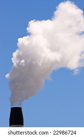 A smoking chimney against a clear blue sky