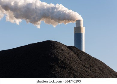 The smoking chimney of a coal power plant against a blue sky with a pile of coal in the foreground.