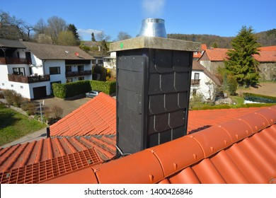 Smoking Chimney with High Grade Steel Fume Hood, covered with natural Slate, on a tiled Roof