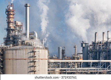 smoking chimneys of oil refinery in winter against a blue sky