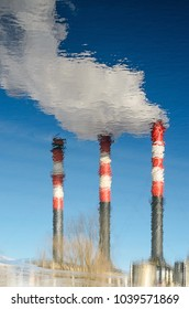The smoking chimneys of the plant are reflected in the water. Plant pipes with smoke against clear blue sky. Abstract background with distortion of reflection on the water surface